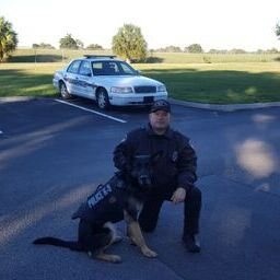 Officer Capetillo sitting next to a police dog.